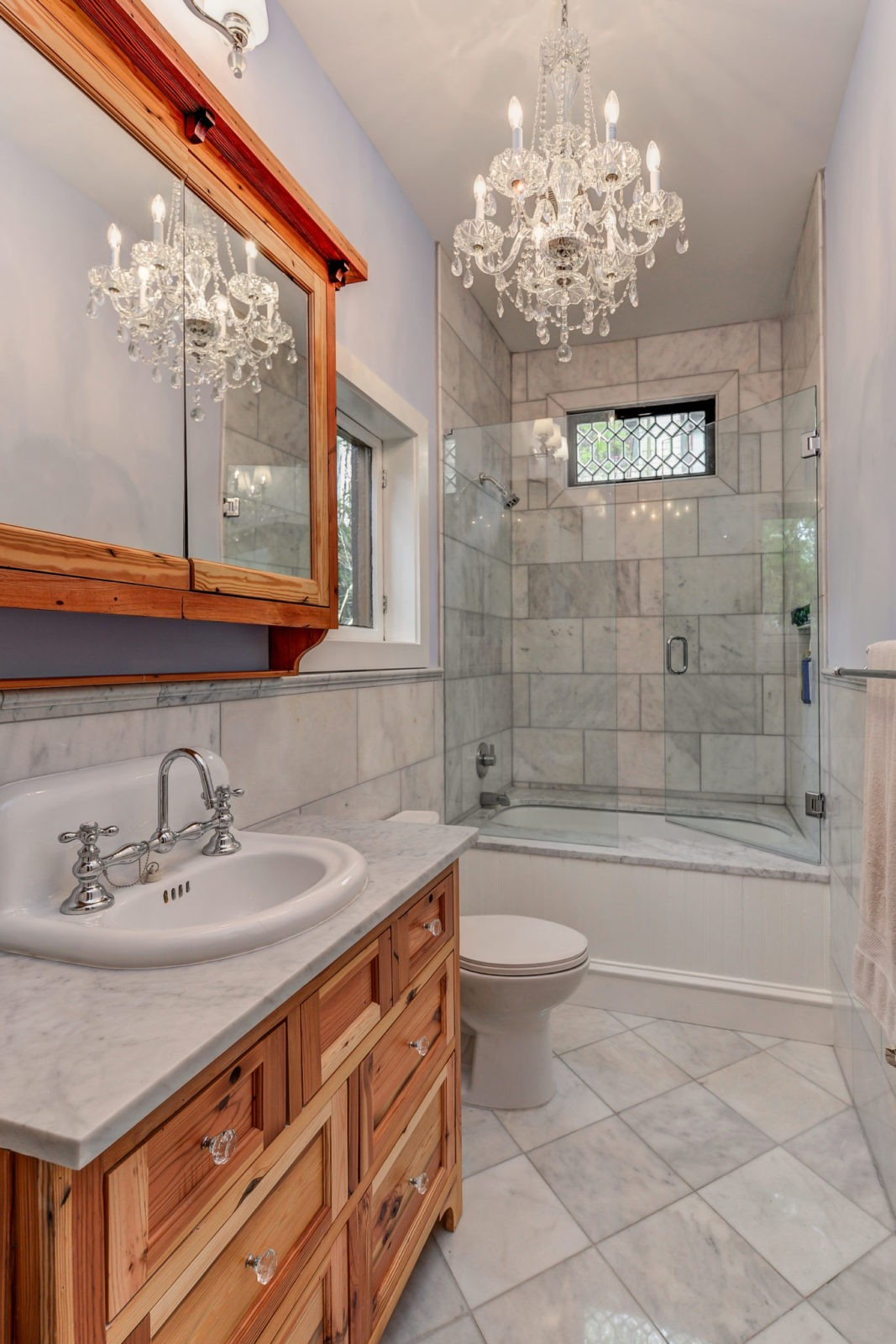 Guest bathroom with marble tile shower and tub, sink and mirror