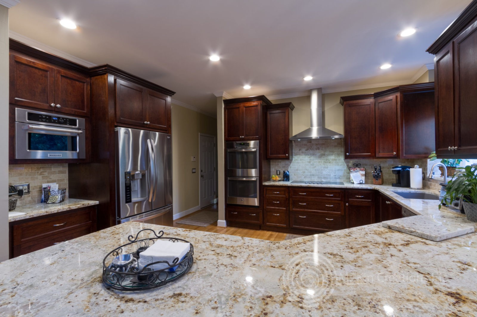 Full view of traditional kitchen with dark stain and light granite countertops.