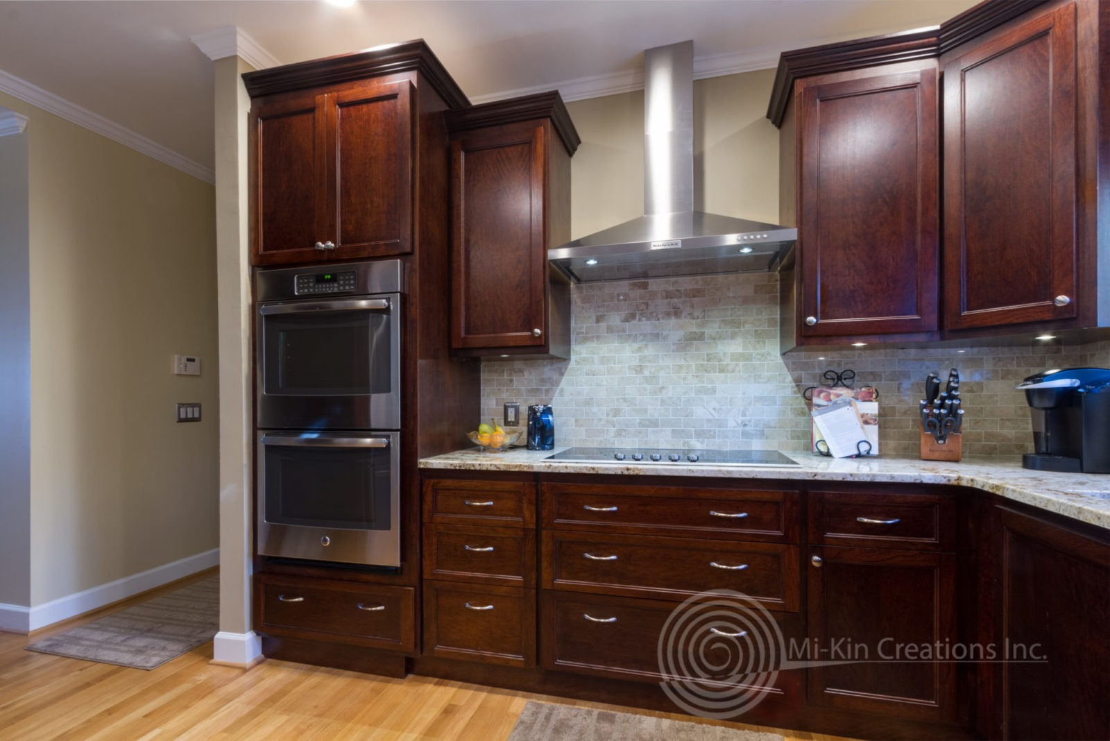 Traditional kitchen cabinets with range and vent hood.